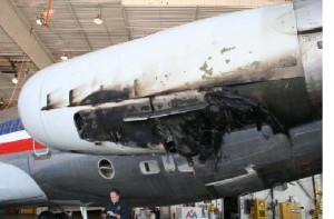 Fire damage to the left engine, including massive hole in bottom of cowling with wires burnt and dangling out.