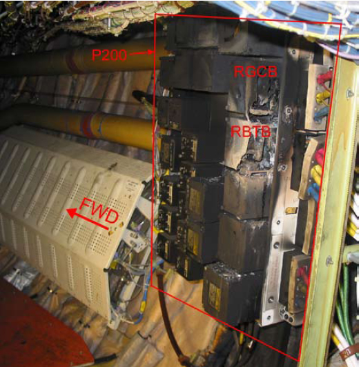 Fire damage to the P200 power panel with cover removed, showing burnt-out RGCB and RBTB contactors (view looking forward and to the right).