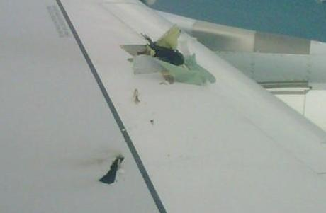 View of the damaged left wing from a cabin window.